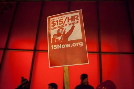 A protest sign is pictured during a rally to raise the hourly minimum wage to $15 for fast-food workers at City Hall in Seattle
